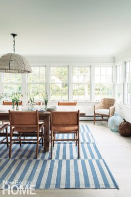 Dining area with leather chairs and a striped rug.