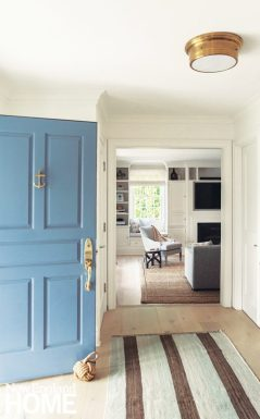 Neutral entryway with a blue door