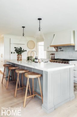 White kitchen with gray island and wood stools.