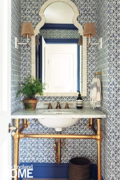Powder room with blue patterned wallpaper.