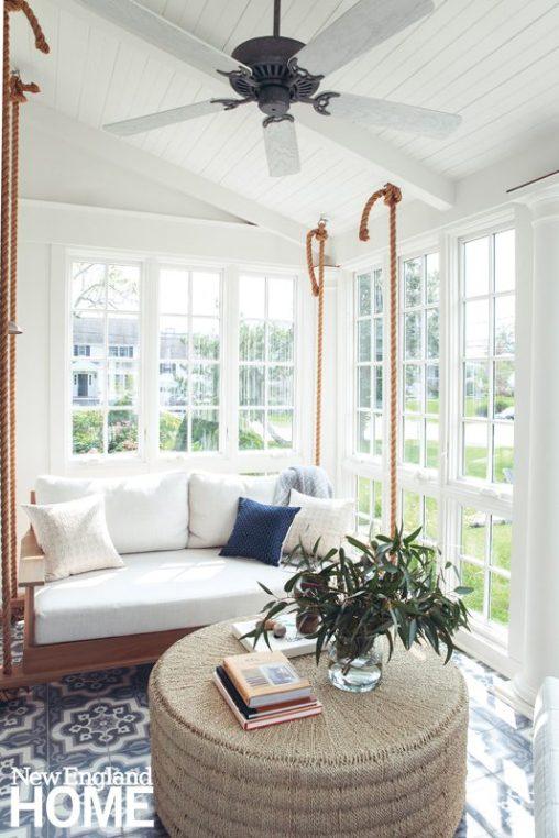White sunroom with bed swing.
