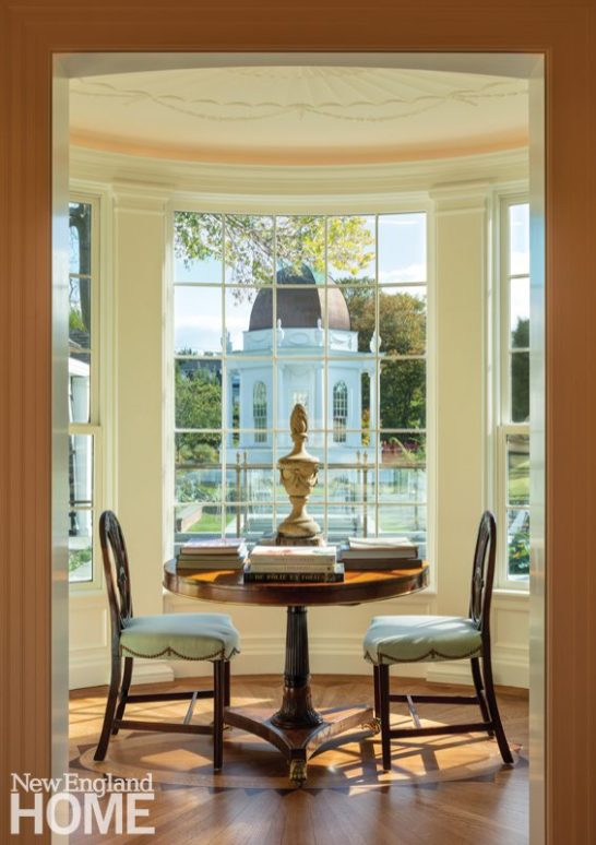 Adamesque elements in the bay window alcove off the library include the oak-and-mahogany floor and the ceiling ornamentation. The period English Sheraton chairs and English Regency rosewood table invite reading by natural light.