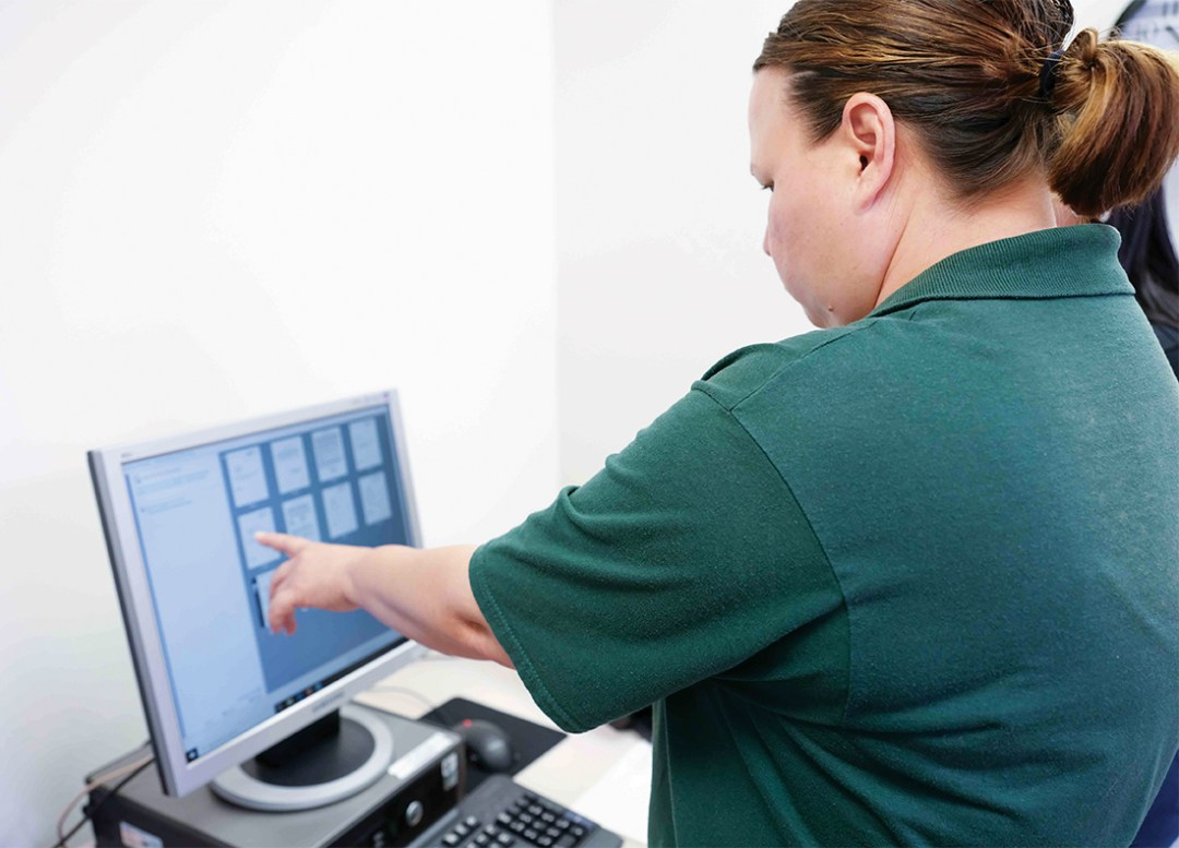 Woman in green shirt pointing to something on the computer