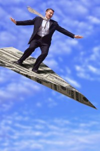 Businessman Flying on Money Airplane