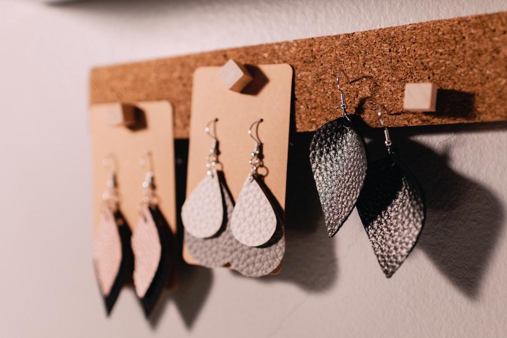 dangle earrings on a corkboard