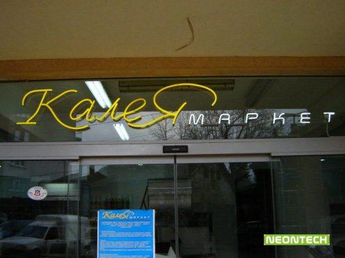 калея маркет неон върху стъклена витрина