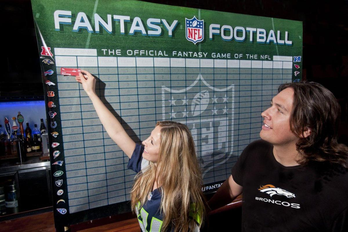 Fantasy football players put selections on a draft board.