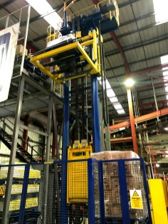 This open sided pallet lift, protected by safety guarding takes pallets off the infeed conveyor and lifts them to a second floor level