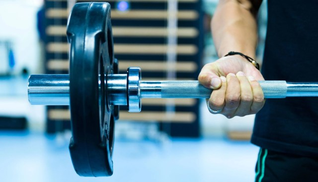 Man with weighted barbell at gym
