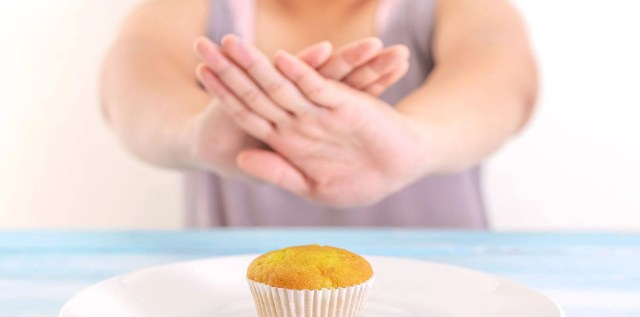A fasting woman not eating a cupcake