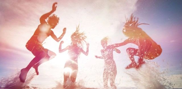 Silhouettes of happy young people jumping in sea