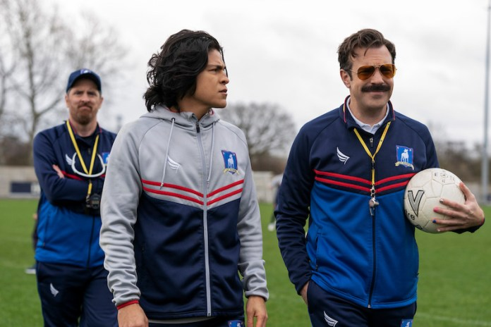 Dani Rojas and Ted Lasso in sunglasses walk on the football pitch in conversation