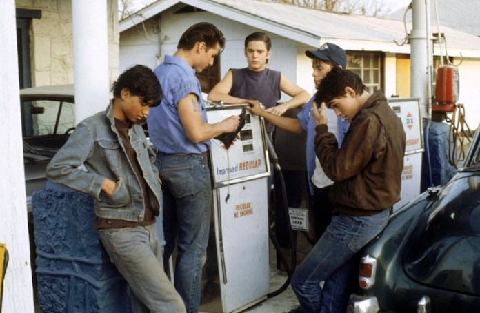 the cast of the outsiders hanging outside of a gas station. Ralph Macchio, Tom Cruise, C. Thomas Howell, Rob Lowe, and Matt Dillon are pictured.