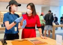 Apple spesialis menjelaskan produk kepada pelanggan di Store saat pandemi COVID-19