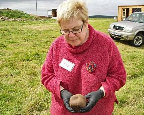 Anne holds the strange stone cube.