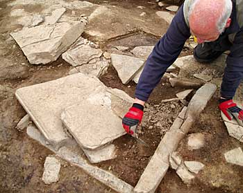 Roy revealing one of the hearths in Structure 8.