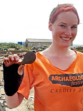 Emily displays the fine polished stone spatula from the levelling deposits under St 7.