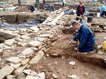 Ray uncovers the basal slabs of the west wall of St 8.