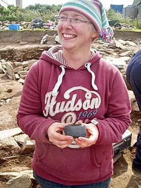 Sarah with her fine polished stone axe discovered under the west dresser of St 10.