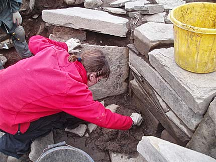 Antonia carefully reveals the  new decorated stone in Structure Twelve.