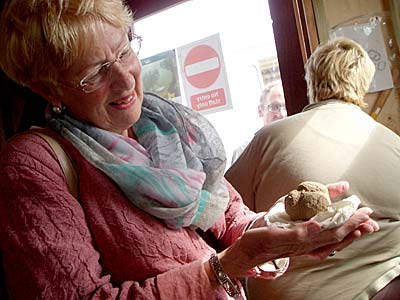 Babette cradles the stone ball just before it is sent south for conservation.