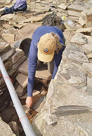 Lesley investigates the drain between Structures One and Nineteen (with modern water pipe above!).