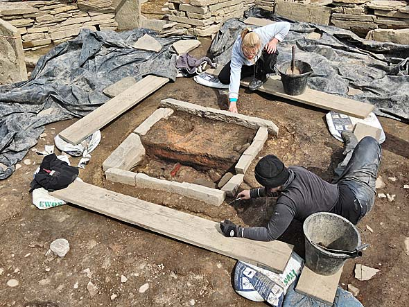 Andy and Erica define the construction cut around the hearth in Structure One.