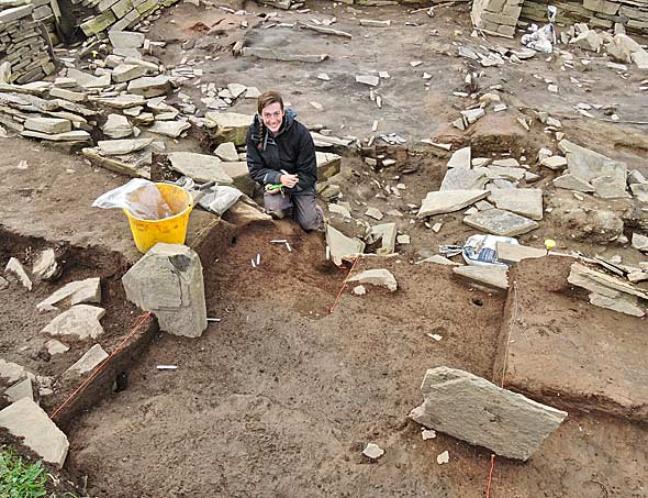 Tansy removes the last of the robbing debris from the newly discovered east entrance to Structure Twelve.