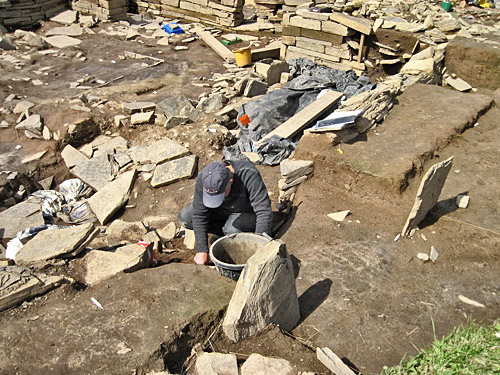 Tom removing more of the infill of the robber trench around the east entrance to Structure Twelve.