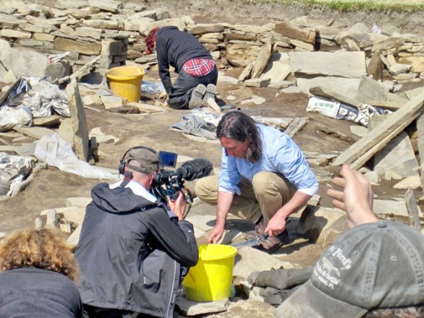 Neil Oliver lends a hand cleaning the floor deposits in Structure Eight.