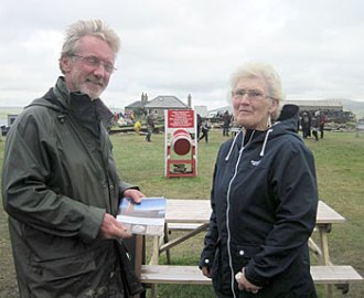 The 1,000th visitor of the day, Melba Shearer, receives a guidebook from site director Nick.