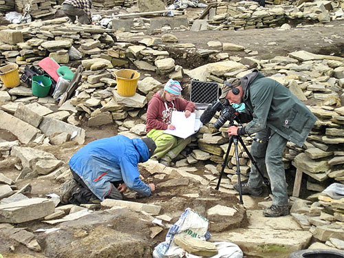 Jasper is closely observed by BBC cameraman Ed as he cleans the bone deposit under the north-east buttress of Structure Ten.