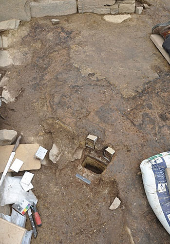 Sampling in Structure One, 2013, at the north side of the central hearth. Two upper sample tins are in place through the then partially excavated Phase 2 deposits, with the sampling sondage showing the depth of the Phase 1 sequence below.
