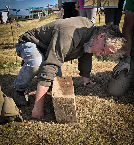 Site director Nick examines the decorated stone after its careful removal from Structure Five this afternoon.