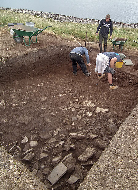 Mike, Declan and Pete at work in Trench Y. The rubble spread at the top of the trench can be seen at the bottom of the picture.
