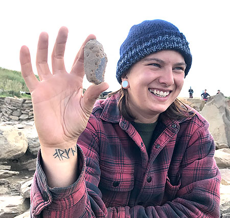 Alice with one of the two finds she recovered from the same section of Structure Eight today - a stone tool and a flint core.