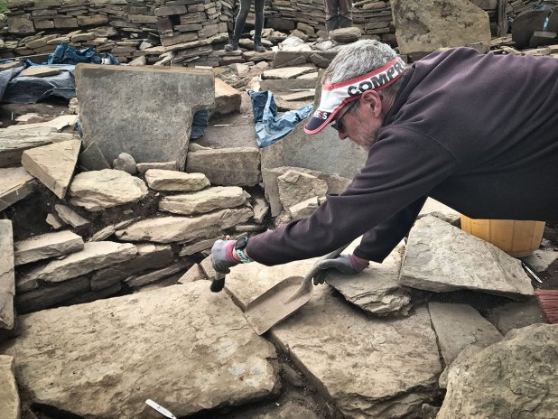 Chris cleans the newly revealed paving between Structure Seventeen (represented by the curving wall) and Structure Eighteen - two buildings earlier than Structure Eight and lying beneath it.