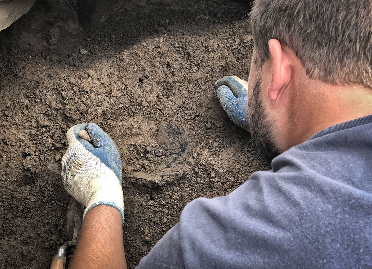Tristan begins excavating a large fragment of pot from the entrance area of Structure Twelve.