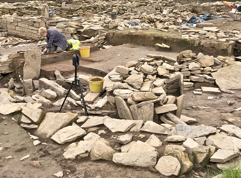 The laser scanner documents Structure Twenty-Six while Christine works on the midden baulk by the eastern entrance to Structure Twelve.