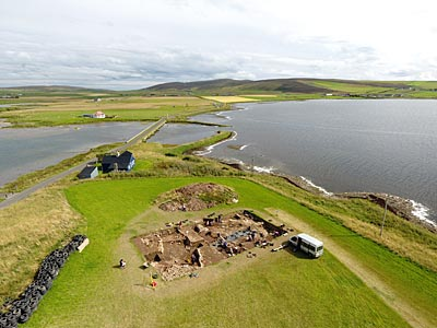 Trench T, looking across the Brig o' Brodgar towards the Stones of Stenness and Barnhouse Neolithic settlement. (Scott Pike)