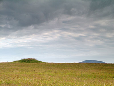 Bronze Age barrow on a ridge of high ground with the top of Ward Hill, Hoy, in the distance. (Sigurd Towrie)