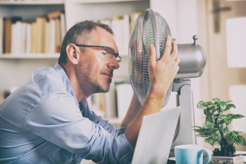 Hombre con calor frente a un ventilador