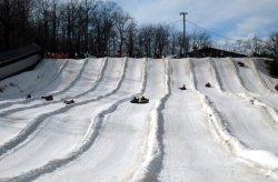 snow tubers race down a snowy hill