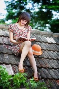 girl reading book on the brick roof