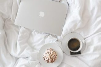 coffee and sweets next to a laptop