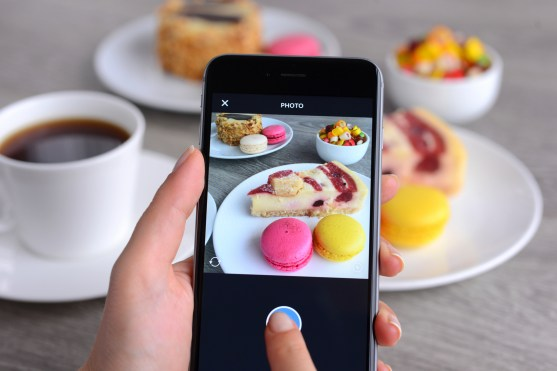 İstanbul, Turkey - January 26, 2016: Woman hands holding an Apple iPhone 6 and taking photos of a food with Instagram application. iPhone is a touchscreen smart phone produced by Apple Inc.