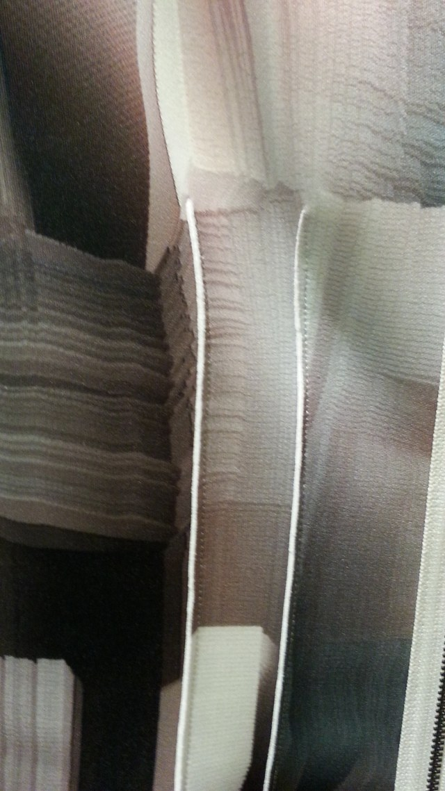 Close up of lapped seam dart on Tahari RTW; the white portion is the solid wrong side of fabric