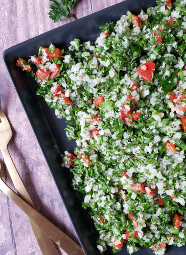 overhead shot of cauliflower tabbouleh a.k.a. tabouli salad on a plate with forks next to it
