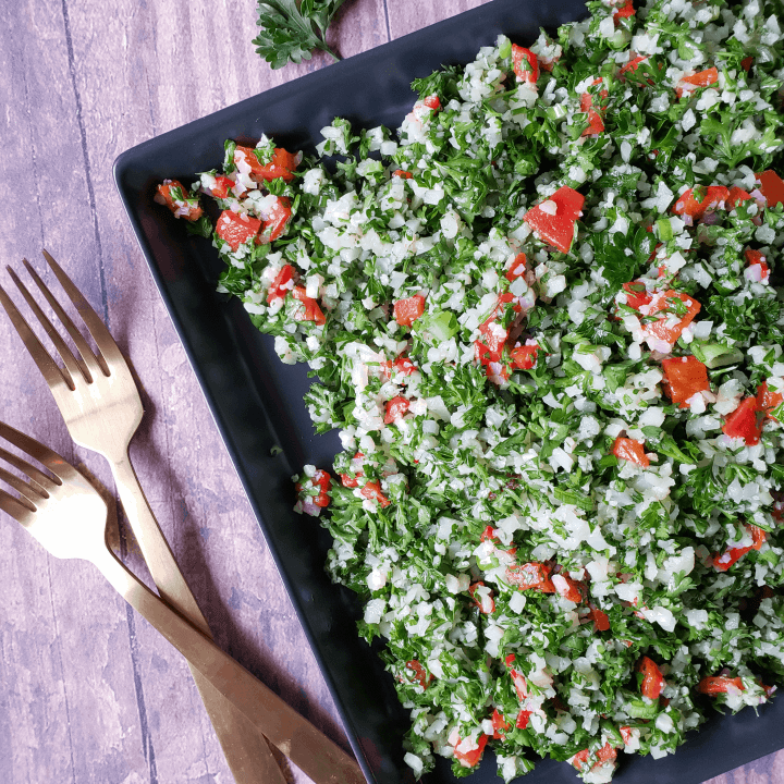 overhead picture of cauliflower tabbouleh a.k.a. tabouli salad on a plate with forks next to it