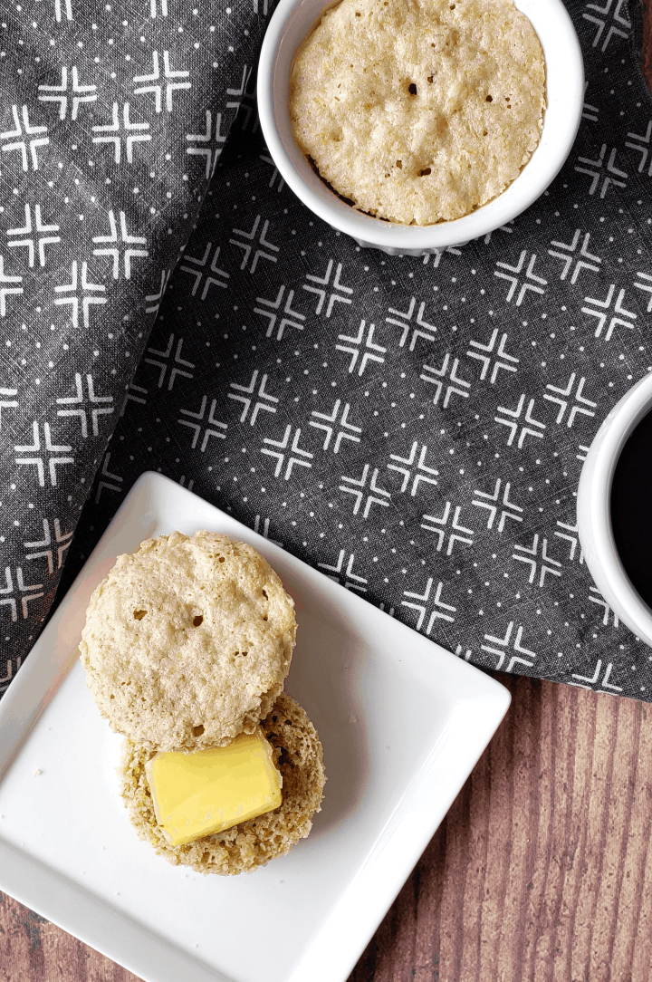 overhead photo of two biscuits or english muffins, one sliced with butter and the other in a ramekin
